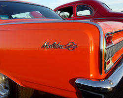 The iconic Malibu SS logo pops against the exquisite orange paint job on this 1964 Chevrolet Chevelle