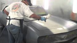 View of Rodney with spray gun in hand painting his Camaro