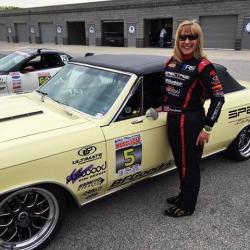View of Lynda Jacobs in her Spectre Performance Driving Suit with her '66 Chevelle Wimpy