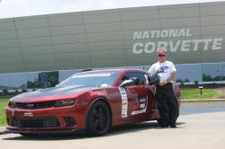 """Photo of Jason Luebcke next to """"Bama"""" in front of the National Corvette Museum sign &"""