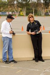 Mary Pozzi with camera in hand having conversation with fellow photographer